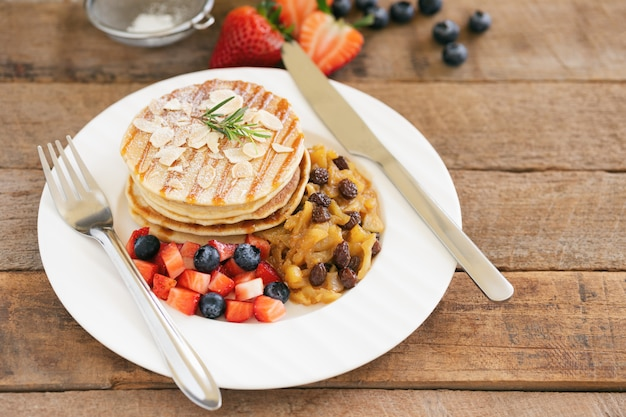 Homemade pancake or hot cake stacked on white plate with fresh fruit and apple raisin sauce on wood table.