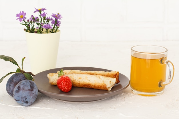 Homemade pancakes filled with cottage cheese, a strawberry on a plate, a cup of tea, plums and flowers.