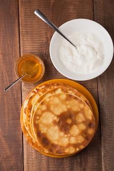 木のテーブルにサワークリームと蜂蜜とプレート上の自家製パンケーキ