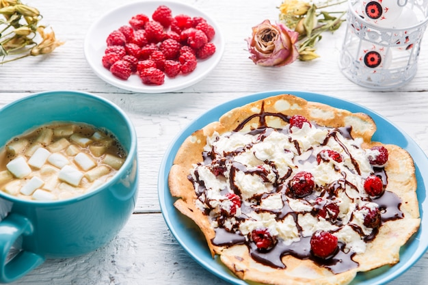 Homemade pancakes or russian pancakes with chocolate sauce, whipped cream and raspberries