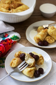 Homemade pancakes stuffed with cottage cheese with raisins, served with sour cream and cherry.