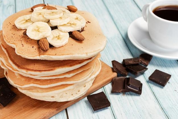 근접에서 커피 한잔과 함께 밝은 파란색 나무 표면에 바나나와 초콜릿으로 만든 팬케이크