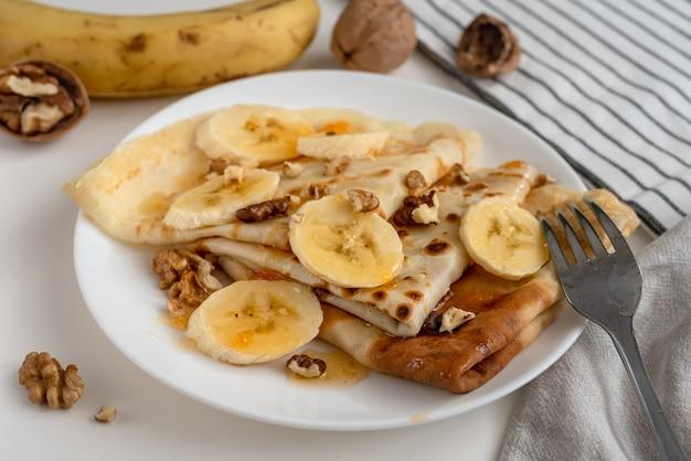朝食にバナナ、ベリーシロップ、クルミを添えた自家製パンケーキ