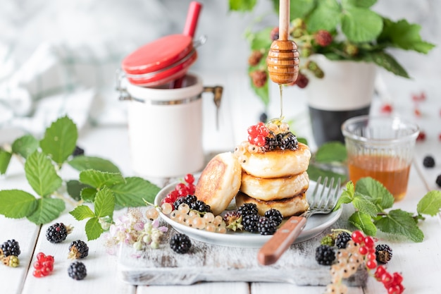 Homemade pancakes with berries and alarm clock on white wooden