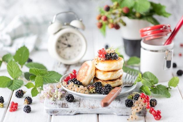 Homemade pancakes with berries, the blackberries, the honey on the plate, a branch of a blackberry alarm clock on white wooden background