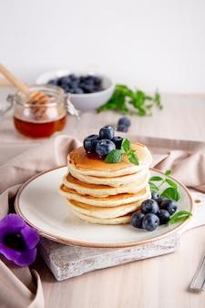 白いテーブルの垂直写真にブルーベリーと粉砂糖を入れた自家製パンケーキ。