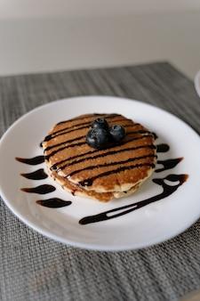 Frittelle fatte in casa con mirtilli sopra e con sciroppo di cioccolato versato sopra