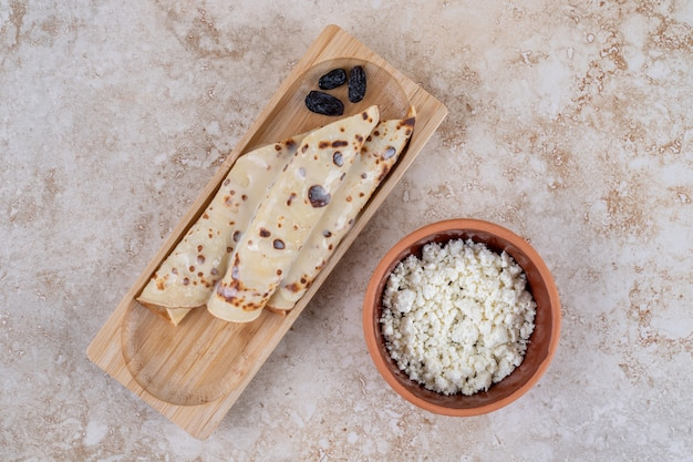 木の板にカッテージチーズを添えた自家製パンケーキ