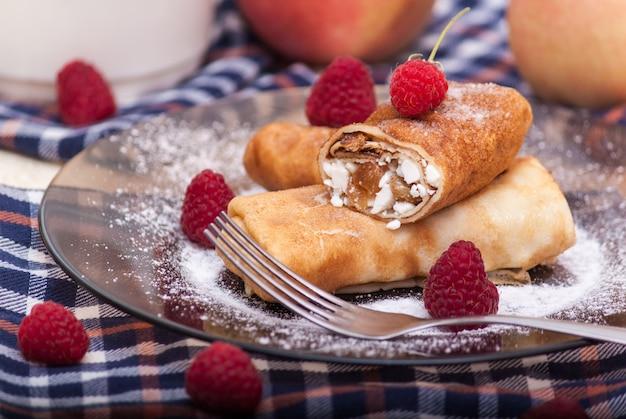 Homemade pancakes with cream cheese, raisins and raspberry on a plate. maslenitsa.