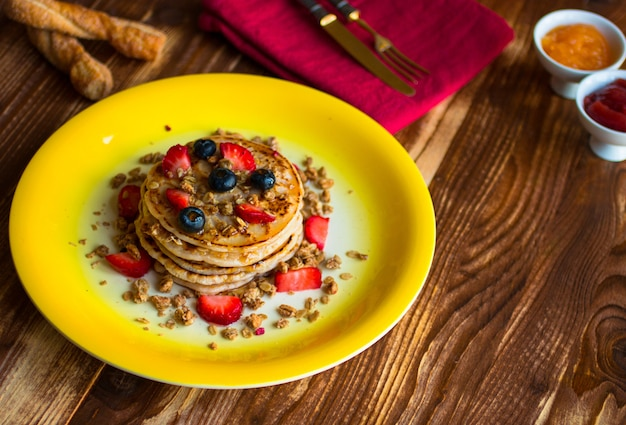 Homemade pancakes with fresh berries, strawberries, blueberries and maple syrup.