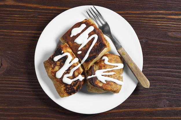 暗い木製のテーブル、上面図に肉とサワークリームと自家製パンケーキ