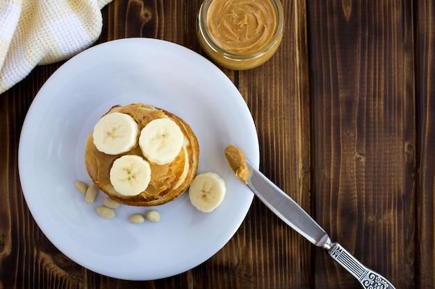 茶色の木製の背景の白いプレートにピーナッツペーストとバナナの自家製パンケーキ。上面図。コピースペース。