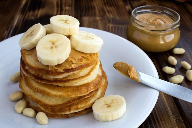 木製の白いプレートにピーナッツペーストとバナナの自家製パンケーキ