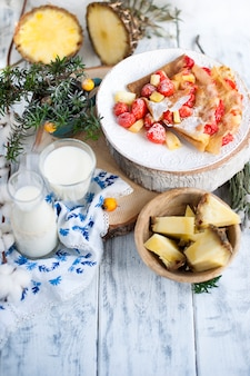 Homemade pancakes with strawberries and pineapple on a white plate with milk