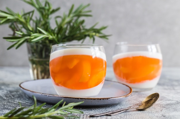 灰色のコンクリートの背景にガラスの瓶に桃と桃のゼリーのスライスと自家製パンナコッタ。