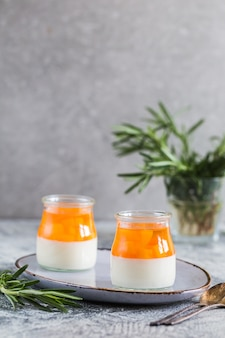 Homemade panna cotta with slices of peach and peach jelly in glass jars on a gray concrete background.