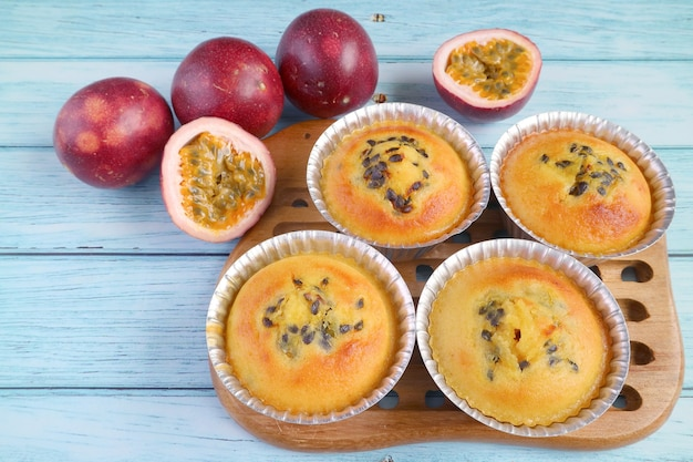 Homemade passion fruit muffins in molds on breadboard with fresh passion fruits on pale blue table