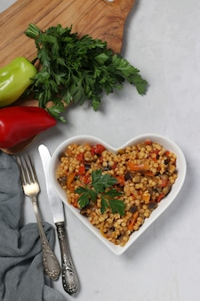 Homemade pasta ptitim with vegetables on heart-shaped plate on gray table. view from above. vertical format