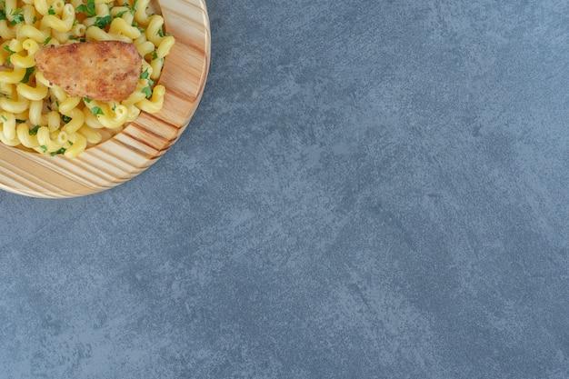 Pasta fatta in casa con pollo sul piatto di legno.