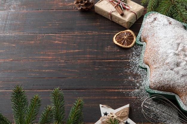 自家製ペストリー、クリスマスツリーの形をしたビスケット、ギフト、トウヒの枝、木製のテーブルの装飾。上面図。
