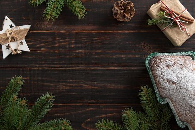 Домашняя выпечка, печенье в форме елки, подарки, еловые ветки и украшения на деревянном столе. вид сверху.
