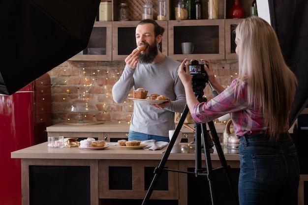 수제 파이. 요리 취미. 신선한 크루아상을 먹는 기쁘게 남자. 백 스테이지 사진. 카메라와 함께 여자입니다.