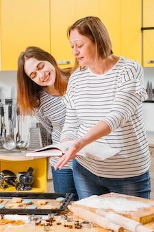 수제 생과자. 엄마와 딸이 비스킷을 준비하고 요리 책의 레시피와 결과를 비교했습니다.