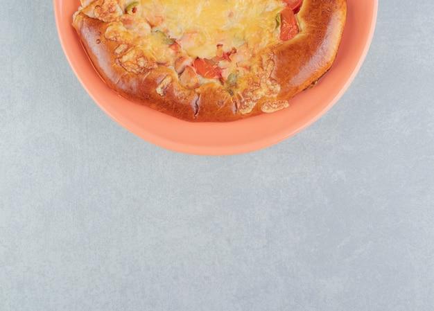オレンジ色のプレートにチーズを添えた自家製ペストリー。