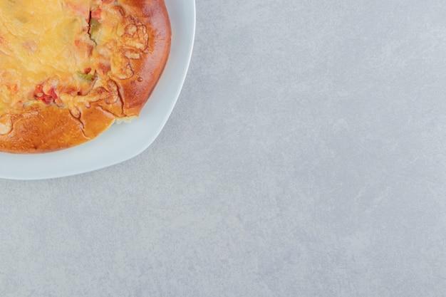 Pasticceria casalinga con formaggio sul piatto bianco.