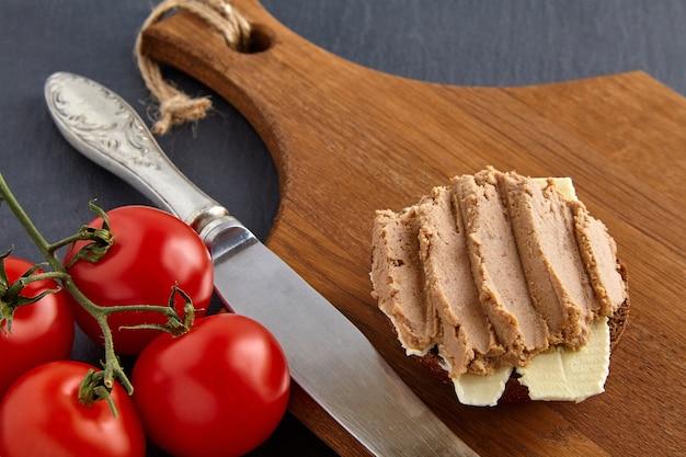 チェリートマトと包丁が付いている石の黒いテーブルの上の木の板の自家製パテサンドイッチ