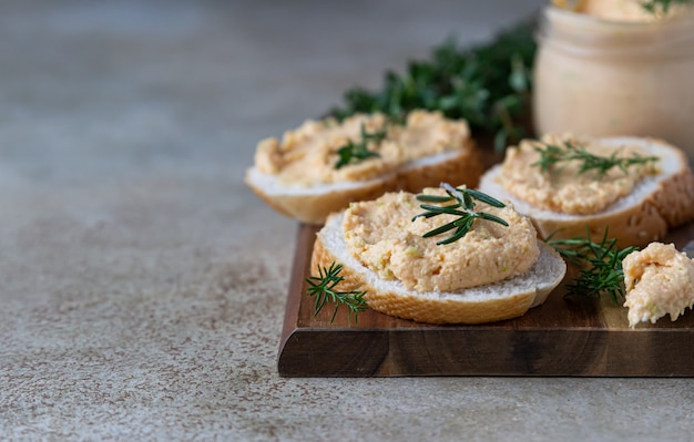 Homemade pate, spread or mousse in glass jar with sliced bread and herbs.