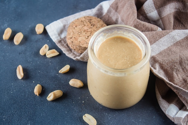 Homemade peanut butter in glass jar and peanuts on blue concrete table background