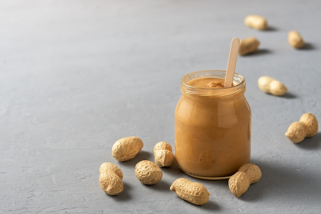 Homemade peanut butter in glass jars on the concrete surface