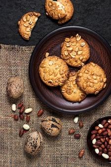 Домашнее арахисовое печенье на коричневой тарелке с сырым арахисом в фоновом режиме. еда в деревенском стиле. плоская планировка, вид сверху