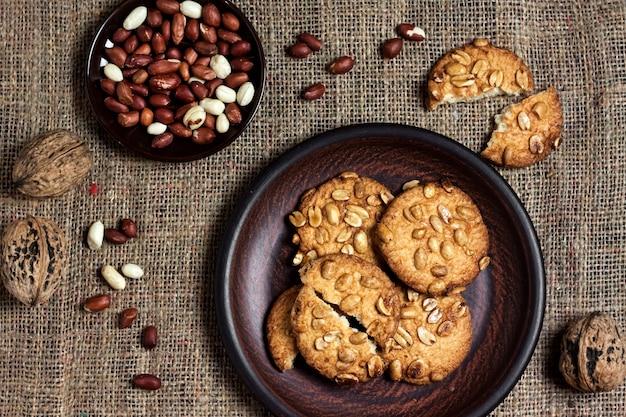 生のピーナッツを背景にした茶色のプレートに自家製ピーナッツクッキー。素朴なスタイルの料理。