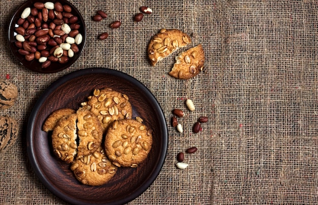 Домашнее арахисовое печенье на коричневой тарелке с сырым арахисом на поверхности. еда в деревенском стиле. плоская планировка, вид сверху, копия пространства