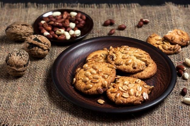 Домашнее арахисовое печенье на коричневой тарелке с сырым арахисом на поверхности. еда в деревенском стиле