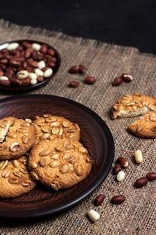 生のピーナッツと茶色のプレート上の自家製ピーナッツクッキー