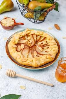アーモンドの葉と新鮮な熟した緑色の洋ナシの自家製梨ガレットパイ