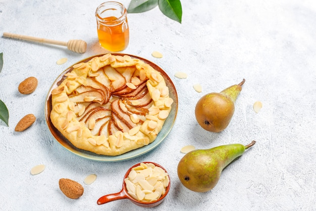 Homemade pear galette pie with almond leaves and fresh ripe green pears