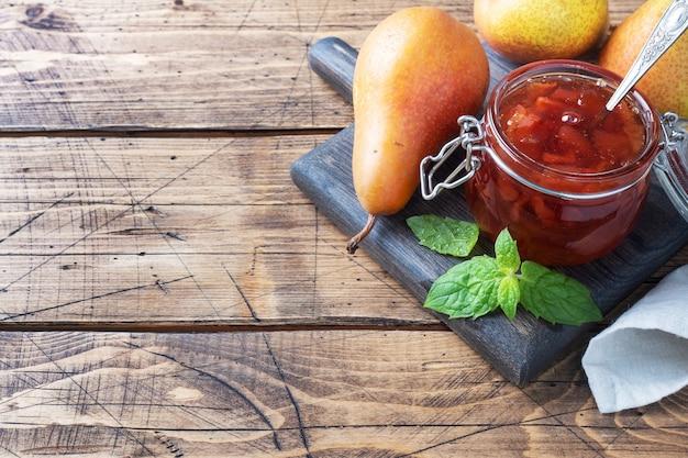 瓶の中の自家製梨ジャムと木製の新鮮な梨