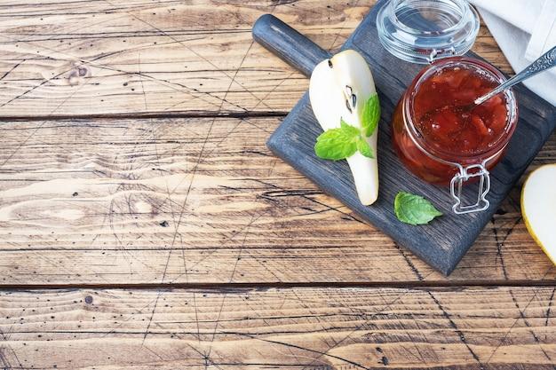 瓶の中の自家製梨ジャムと木製の新鮮な梨 Premium写真