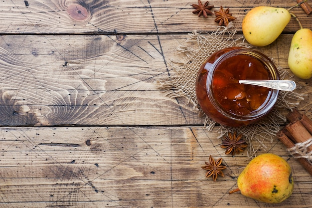 Homemade pear jam in a jar and fresh pears on a wooden background