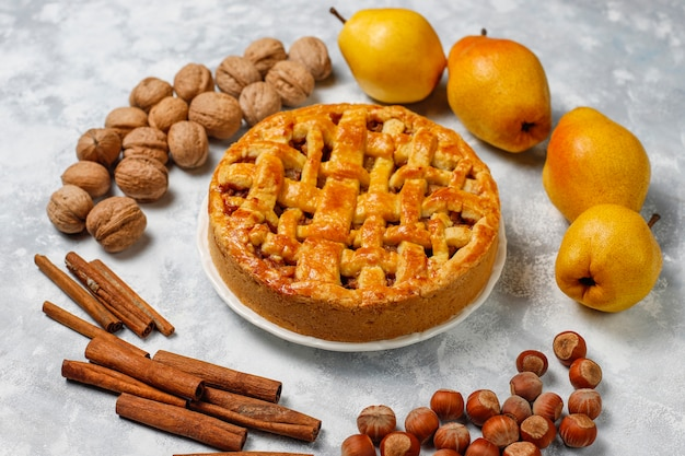 Homemade pear pie with cinnamon and walnuts on light