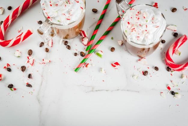 집에서 만든 박하 모카, 사탕 지팡이, 휘핑 크림, 민트 시럽, 흰색 대리석 테이블에 크리스마스 커피 음료, 복사 공간
