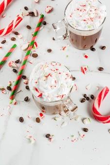 집에서 만든 박하 모카, 사탕 지팡이, 휘핑 크림과 민트 시럽, 흰색 대리석 테이블에 크리스마스 커피 음료
