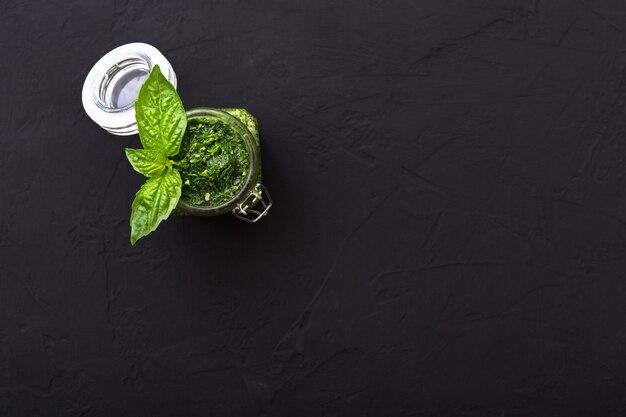 暗いセメントの背景に自家製ペストソースと緑のバジル。パスタ、スパゲッティ用のガラス瓶に入ったイタリアングリーンペストソース。ベジタリアンの健康食品。上面図、テキスト用のコピースペースを備えたフラットレイ。