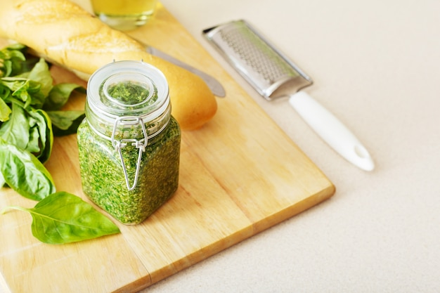 Homemade pesto sauce in glass jar with basil, ingredients and baguette on white table in kitchen.