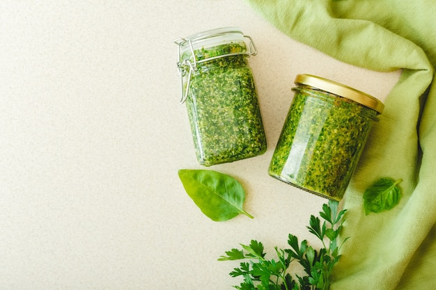 Homemade pesto sauce in glass jars with basil on white table in kitchen with towel. pesto traditional italian sauce