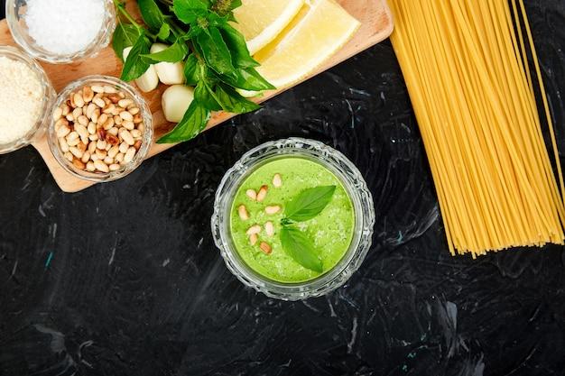 Домашний соус песто в стеклянной банке с ингредиентами.